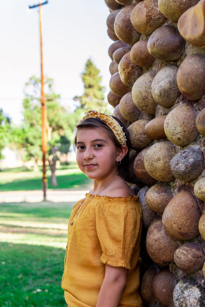 young girl in a yellow shirt and headband standing against a rock wall
