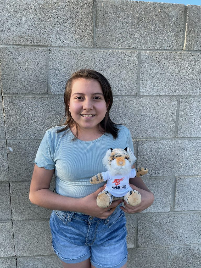 young girl in a blue shirt and jeans holding a stuffed tiger